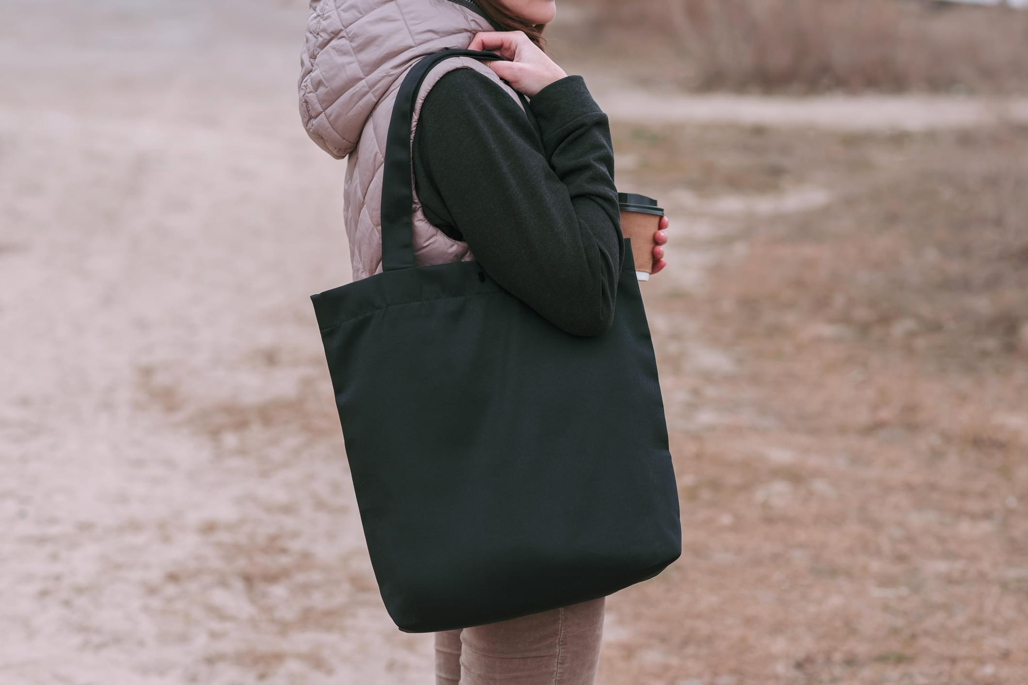Young woman with black cotton bag and paper coffee cup in her hands. Mock up for design.