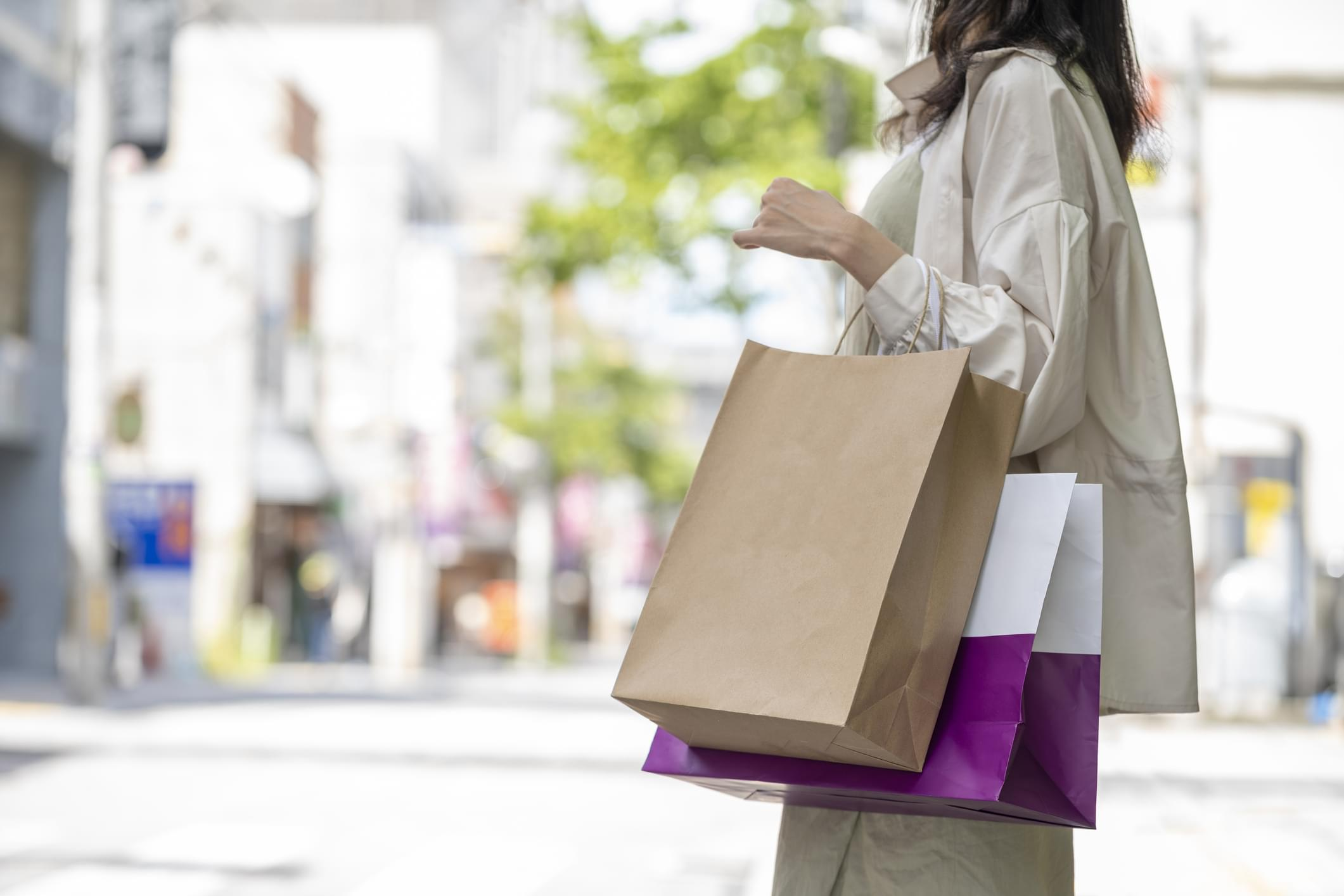 Hands of woman with many shopping bags at shopping