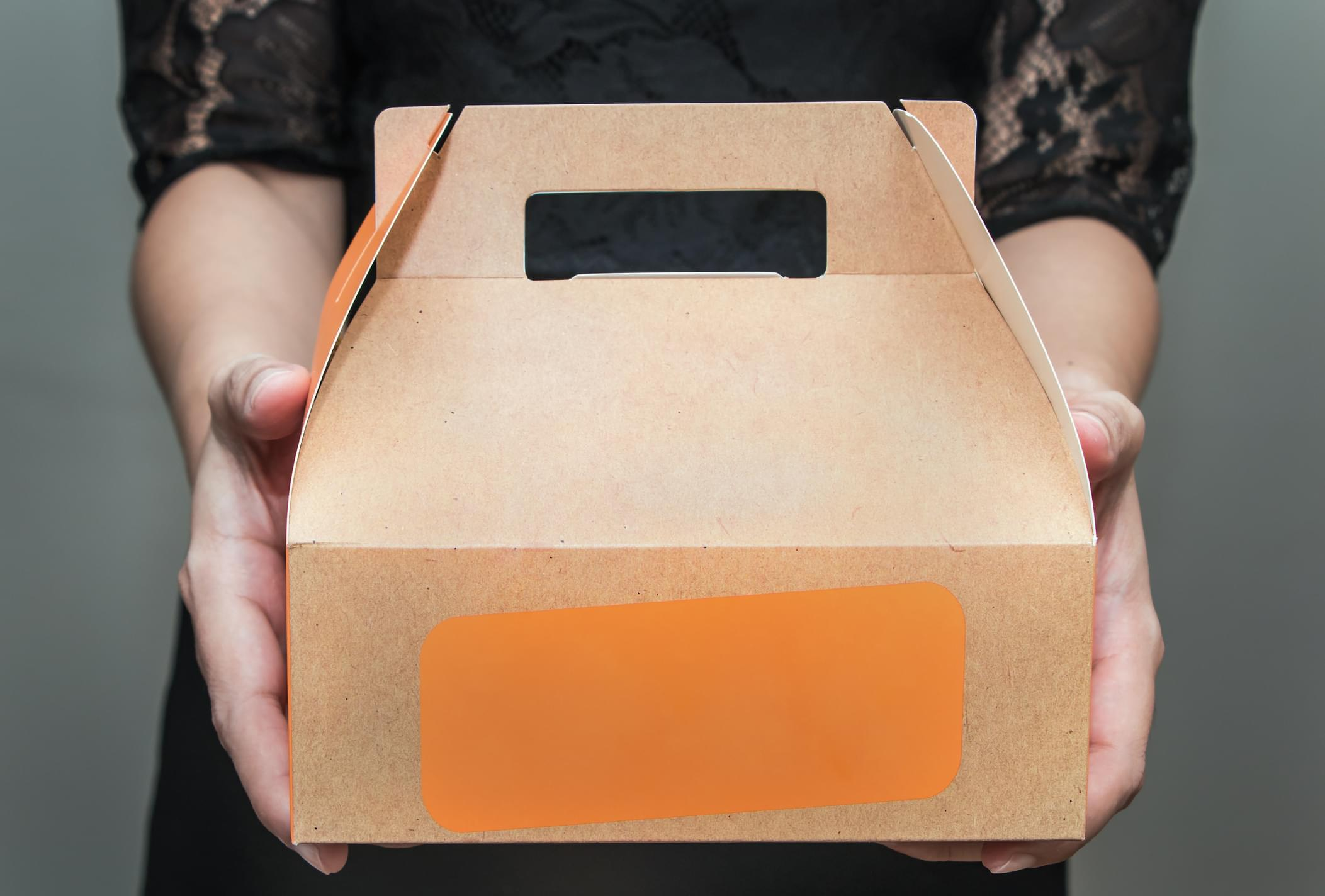A woman in black dress stood bringing a snack box