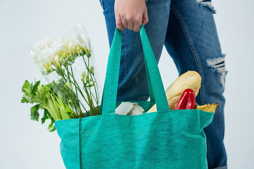person holding a green grocery tote bag